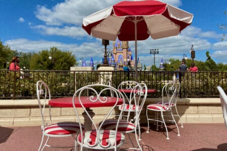 Outdoor table and seating at Disney's Magic Kingdom in front of castle.