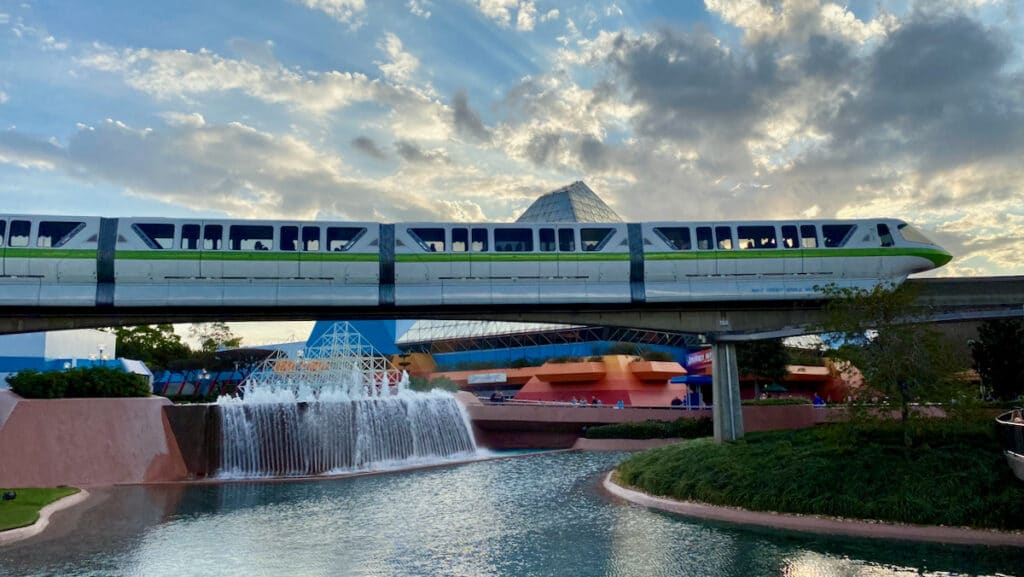 Disney World Transportation Monorail Lime going through EPCOT at sunset.